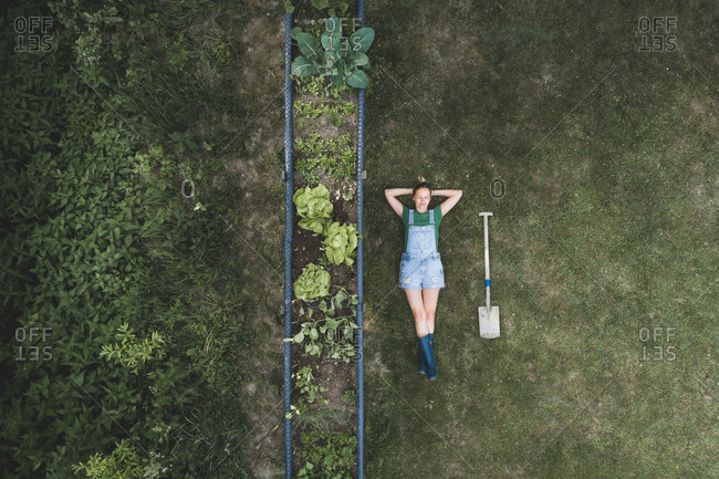 Aerial view of woman lying by raised bed on land in yard