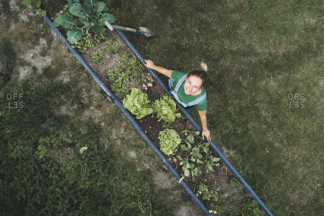 Drone shot of smiling woman standing by raised bed in yard