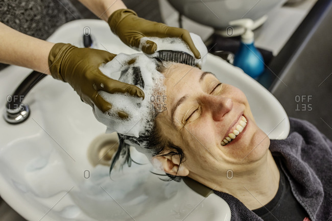 Woman in hair salon getting hair washed with brushes