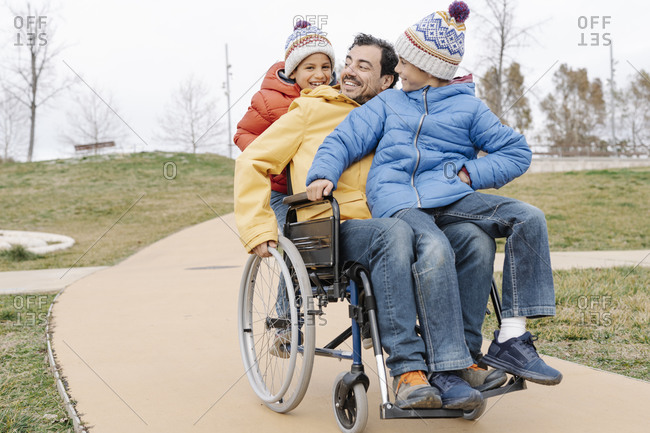 Happy man with playful sons riding wheelchair on footpath at park
