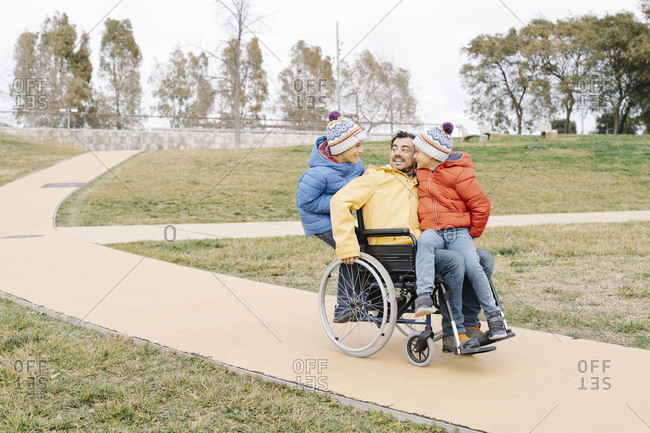 Playful man with excited sons riding wheelchair on footpath in park