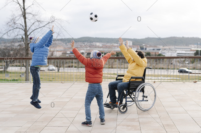 Playful father sitting on wheelchair throwing ball towards enthusiastic sons in park