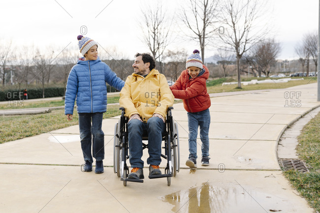 Sons talking and assisting father sitting on wheelchair in park