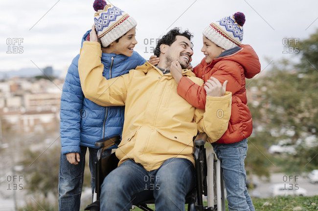Loving father embracing sons while sitting on wheelchair in park