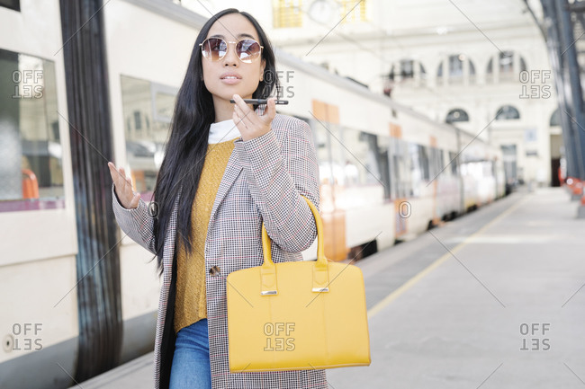 Woman wearing sunglasses talking over smart phone while standing at railroad station