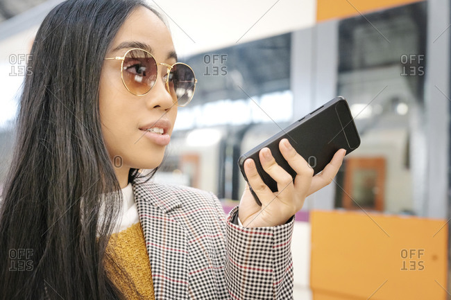 Close-up of woman wearing sunglasses talking over smart phone at railroad station
