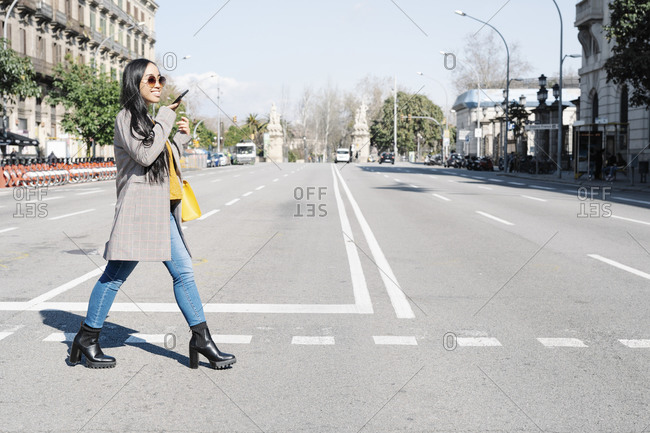 Stylish young woman talking over smart phone while crossing road in city
