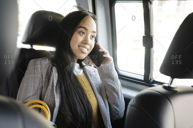 Young woman talking over smart phone while sitting in car