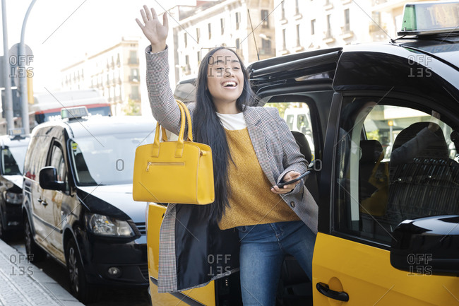 Cheerful young woman waving hand while entering in taxi