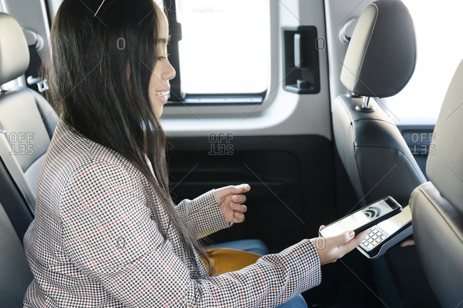 Young woman making mobile payment while sitting in taxi
