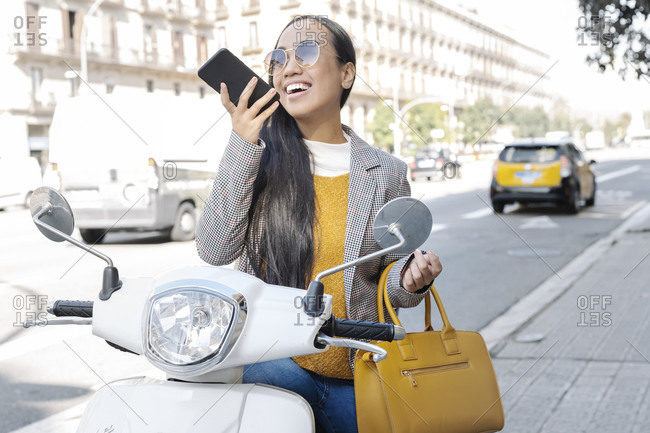Cheerful young woman talking over smart phone while sitting on motor scooter