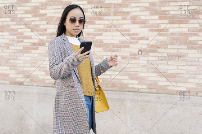 Stylish young woman wearing sunglasses using smart phone while standing against wall in city