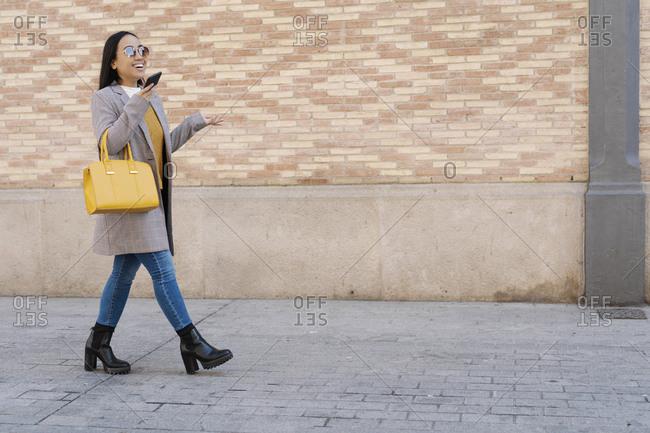 Stylish woman wearing sunglasses talking over smart phone while walking on sidewalk in city