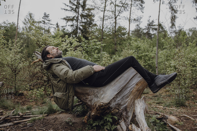 Mature hiker lying on stump in the forest