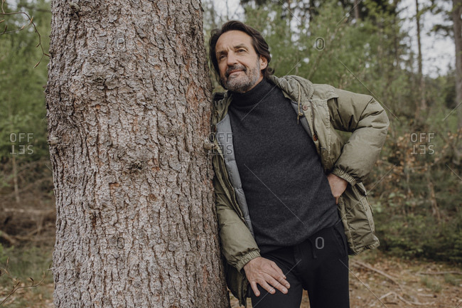 Mature hiker leaning on tree trunk