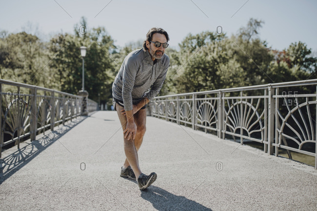 Man wearing sunglasses stretching leg while standing on footbridge during sunny day