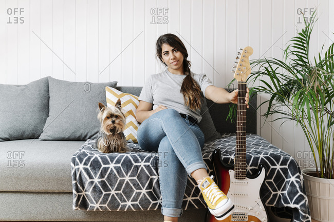 Confident woman holding electric guitar while sitting with Yorkshire Terrier on sofa at home