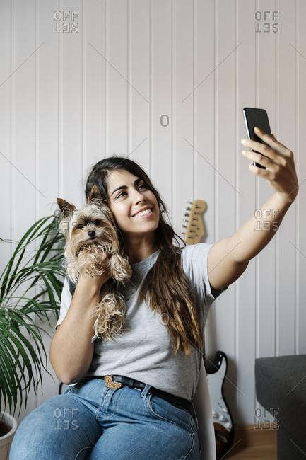 Young woman taking selfie with Yorkshire Terrier while sitting on chair at home