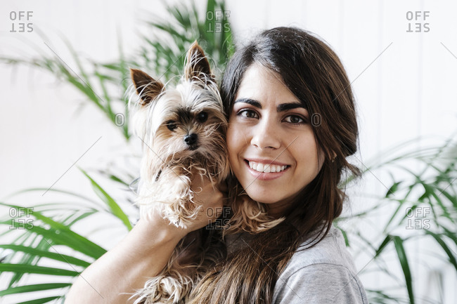 Happy young woman carrying Yorkshire Terrier at home