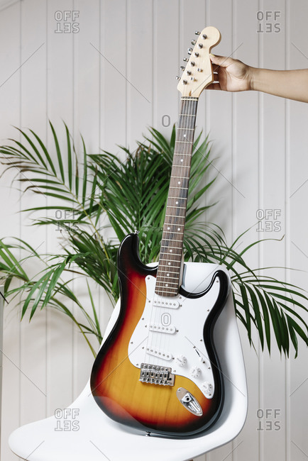 Cropped image of woman's hand holding electric guitar on chair at home