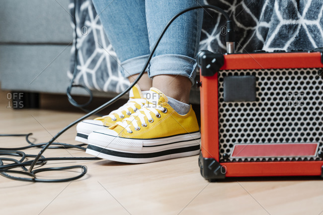 Woman's legs by amplifier on hardwood floor at home