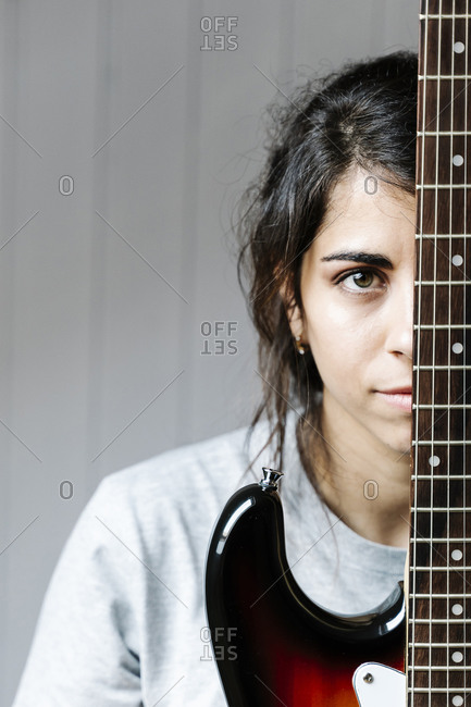 Young woman hiding behind electric guitar against wall at home