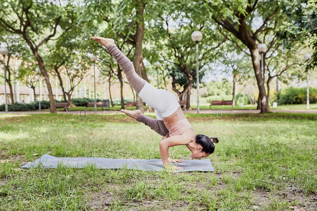 Mid adult woman practicing yoga on mat in park- crow pose