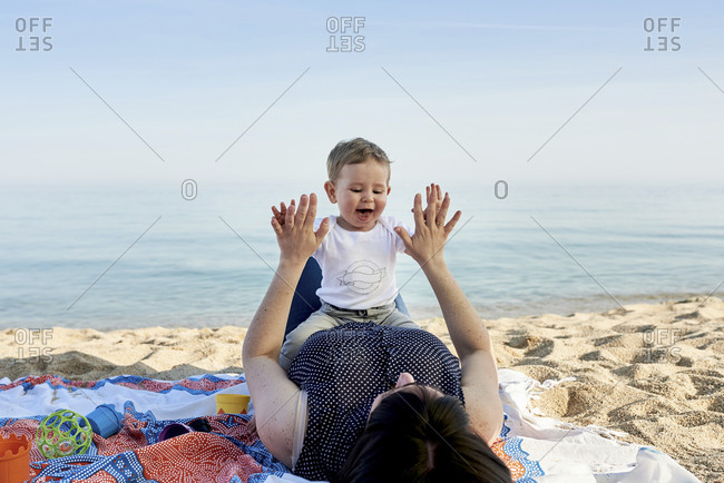 Mother playing clapping game with son while lying on blanket at beach against sea