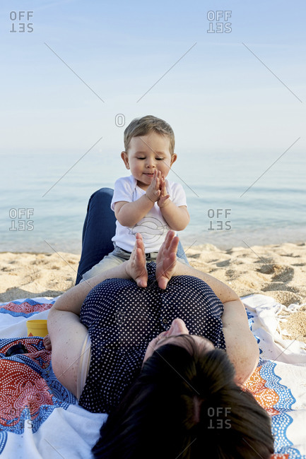 Mother playing clapping game with cute son while lying on blanket at beach against sea