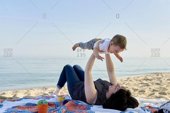 Mother picking up happy son while lying on blanket at beach against sea