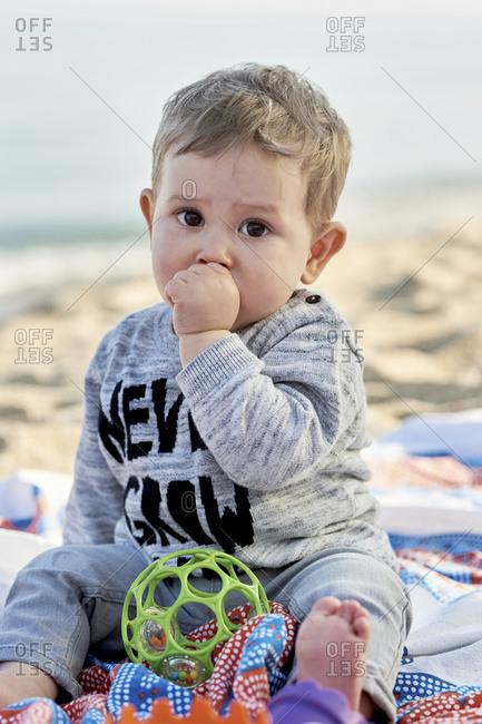 Cute boy sucking thumb while sitting on blanket at beach