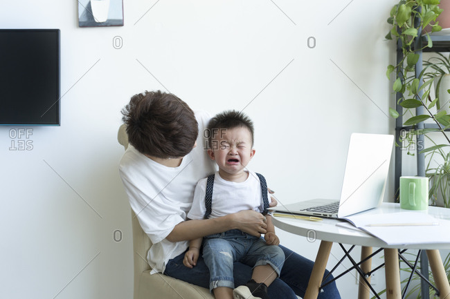 Mother holding crying boy on lap while sitting over chair at home