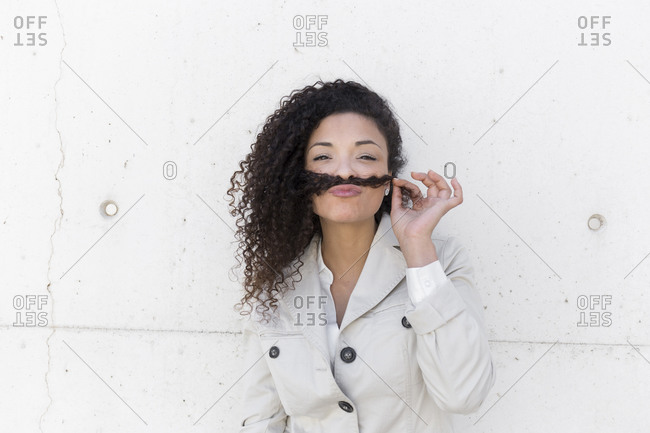 Stylish businesswoman holding hair on lips like mustache against wall
