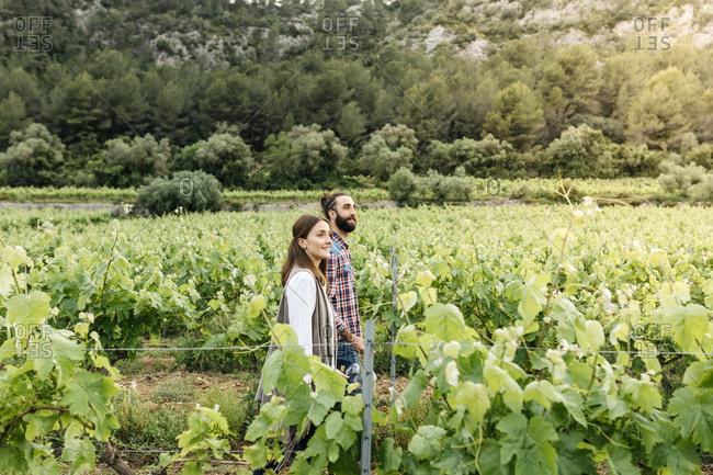 Couple walking in lush vineyard