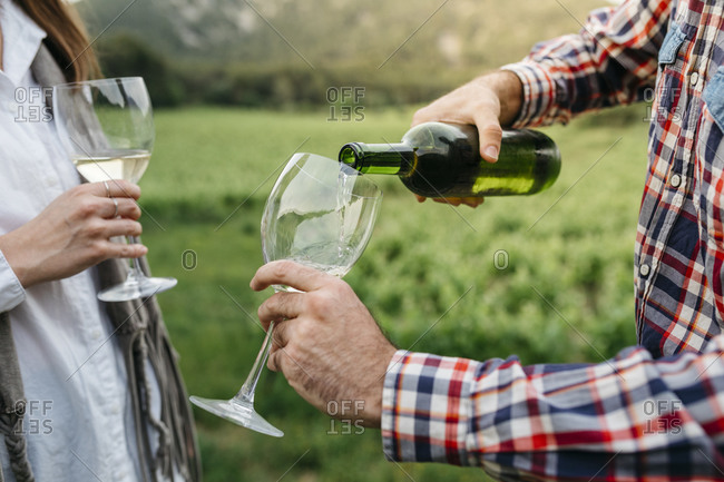 Man serving white wine in glass while standing with woman at vineyard