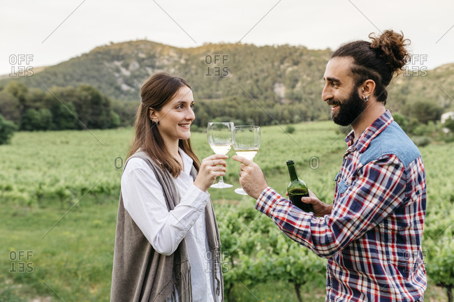 Happy couple toasting wineglasses at vineyard