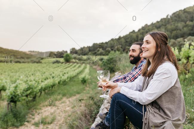 Happy couple holding white wine glasses while sitting at vineyard