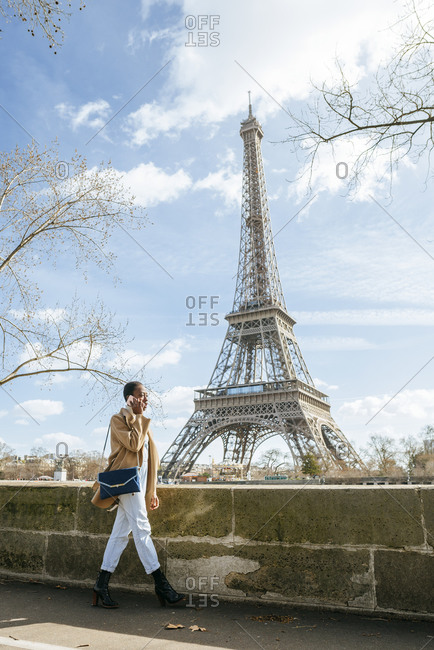 Woman using smart phone while walking on bridge with Eiffel Tower in background- Paris- France