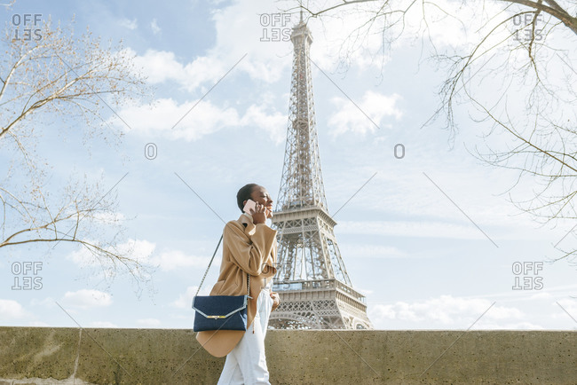 Young woman using smart phone while walking on bridge with Eiffel Tower in background- Paris- France