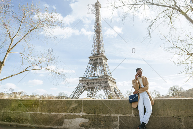 Woman using smart phone while standing on bridge with Eiffel Tower in background- Paris- France