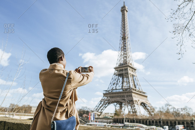 Woman photographing Eiffel Tower through smart phone against sky- Paris- France