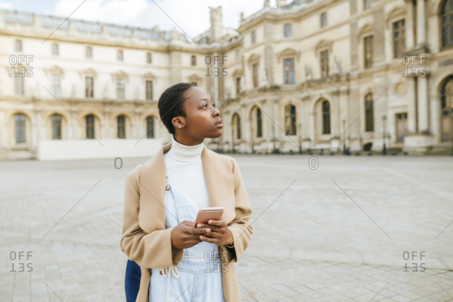Thoughtful woman holding smart phone at town square with building in background at Paris- France