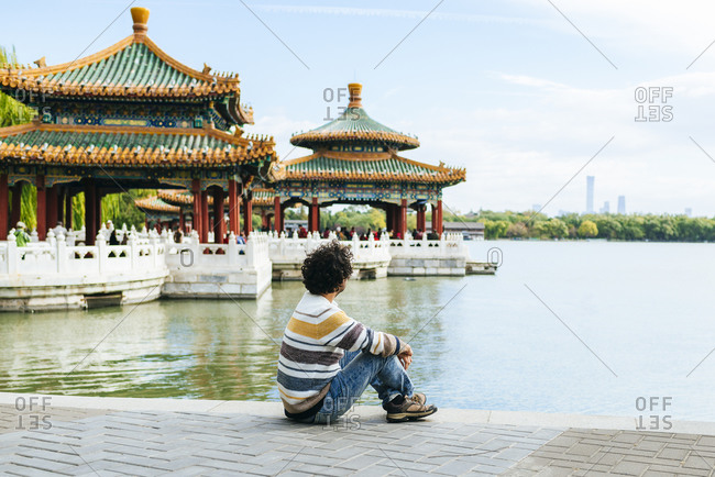 Man sitting on footpath by lake in Beihai Park- Beijing- China