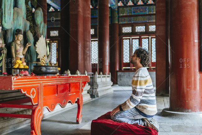 Mid adult man praying in Buddhist temple at Beihai Park- Beijing- China