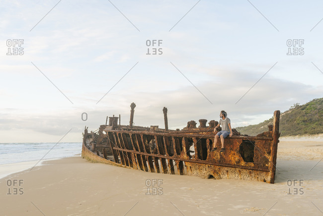 Man sitting on Maheno shipwreck at Fraser Island- Queensland- Australia