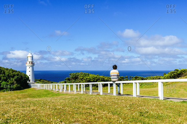 Man sitting on railing against blue sky- Cape Otway- Victoria- Australia