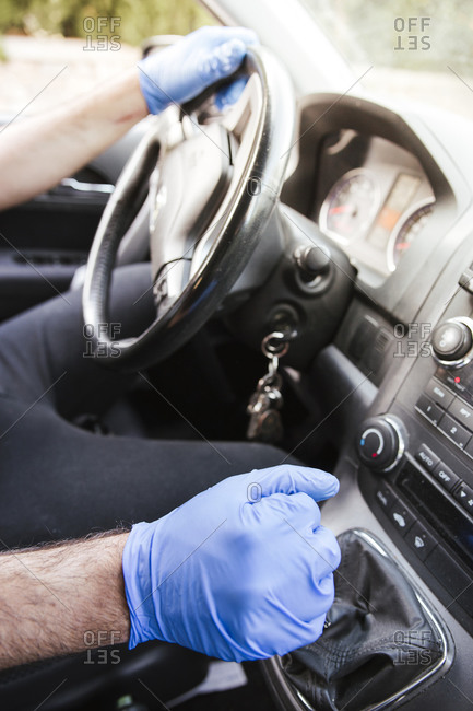Hands of man wearing gloves driving car