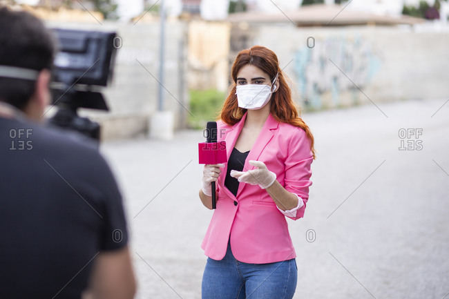 Man filming reporter wearing mask while standing on road