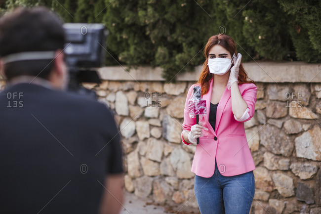 Camera operator filming reporter with microphone wearing mask while standing against wall