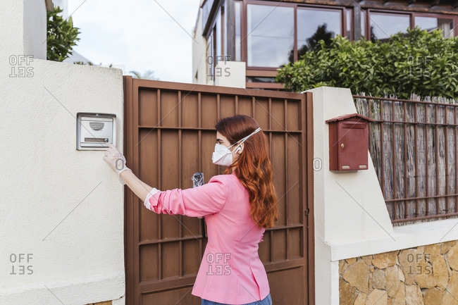 Female reporter wearing mask standing by closed gate